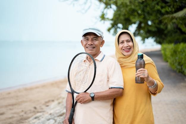 Älterer asiatischer mann und frau, die mit schläger lächeln