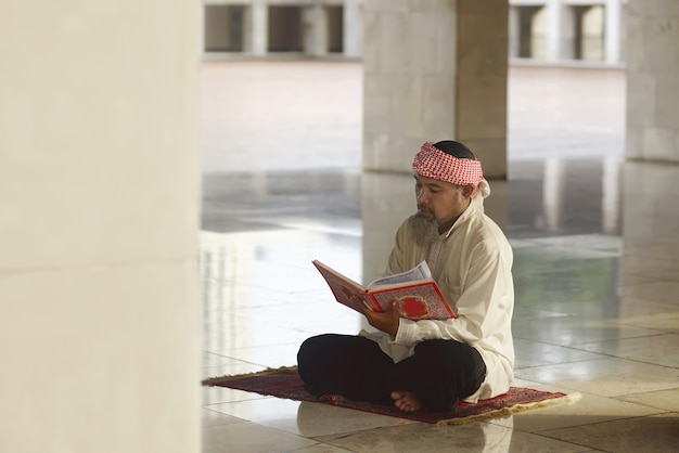 Älterer asiatischer moslemischer mann, der den koran liest