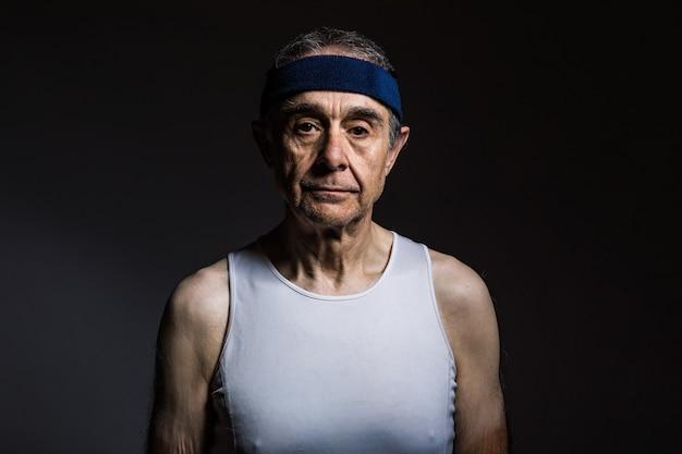 Älterer athlet mit weißem ärmellosem hemd mit sonnenflecken an den armen und blauem stirnband auf dunklem hintergrund. sport- und siegkonzept.