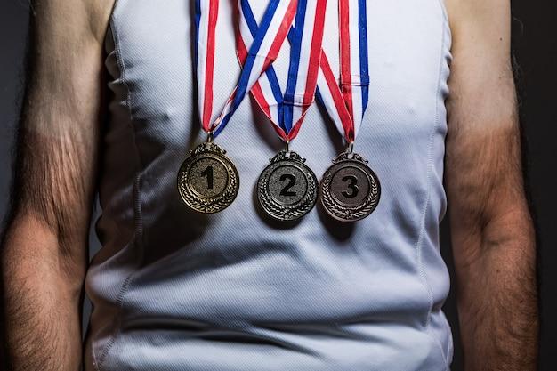 Älterer athlet mit weißem tanktop, mit sonnenflecken an den armen, mit drei medaillen am hals, die sie auf dunklem hintergrund zeigen. sport- und siegeskonzept