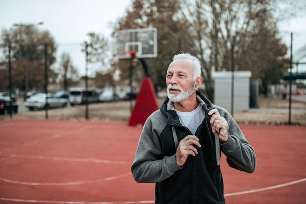 Älterer athlet vor einem lauf stadion im im freien.