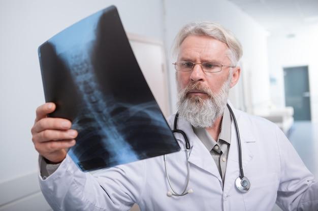 Älterer bärtiger arzt, der die knochenröntgenaufnahme eines patienten betrachtet