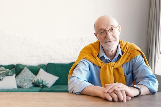 Älterer bärtiger geschäftsmann, der stilvolle elegante kleidung trägt, die an seinem schreibtisch im modernen innenraum mit couch im hintergrund sitzt. menschen, lifestyle, altern, business, freizeit und modekonzept