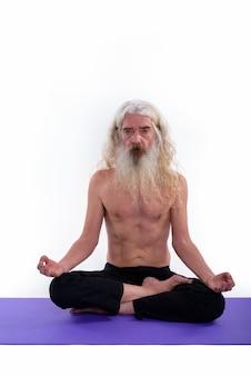 Älterer bärtiger guru mann, der hemdlos meditiert