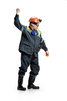 Älterer bärtiger männlicher bergmann, der an der kamera auf einem weiß steht