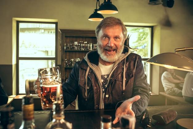 Älterer bärtiger mann, der alkohol in der kneipe trinkt und ein sportprogramm im fernsehen sieht. ich genieße meinen lieblingsbrot und mein lieblingsbier. mann mit bierkrug, der am tisch sitzt. fußball- oder sportfan. konzept der menschlichen emotionen
