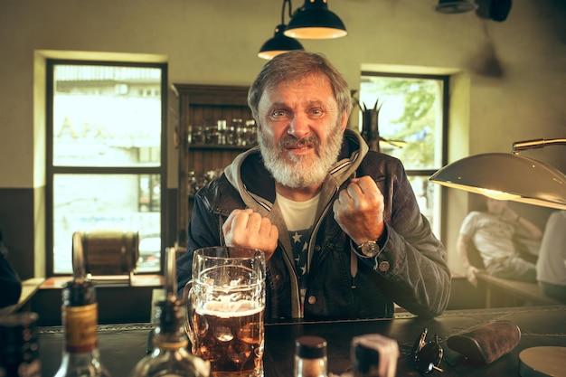 Älterer bärtiger mann, der alkohol in der kneipe trinkt und ein sportprogramm im fernsehen sieht. ich genieße meinen lieblingsbrot und mein lieblingsbier. mann mit bierkrug, der am tisch sitzt.