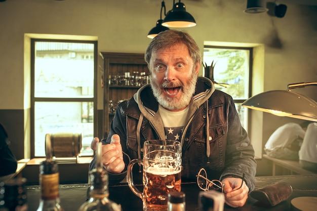 Älterer bärtiger mann, der alkohol in der kneipe trinkt und ein sportprogramm im fernsehen sieht.