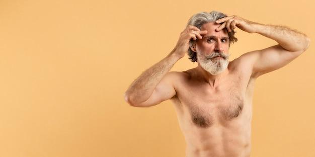 Älterer bärtiger mann, der auf falten mit kopierraum hinweist