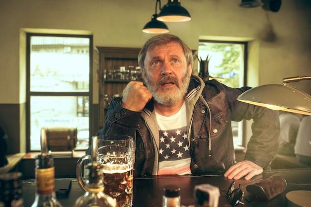 Älterer bärtiger mann, der bier in der kneipe trinkt