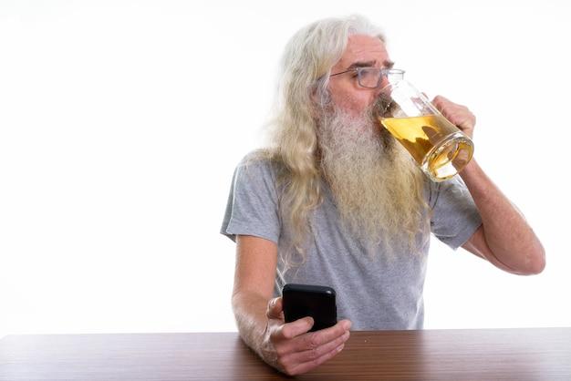 Älterer bärtiger mann, der handy und getränk hält