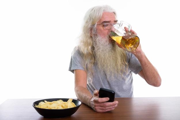Älterer bärtiger mann, der handy während des getränks benutzt