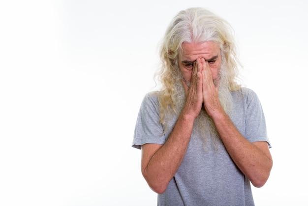 Älterer bärtiger mann, der weint, während gesichtgesicht bedeckt