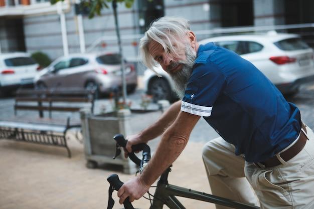 Älterer bärtiger mann, der zur kamera schaut, die fahrrad auf stadtstraßen fährt