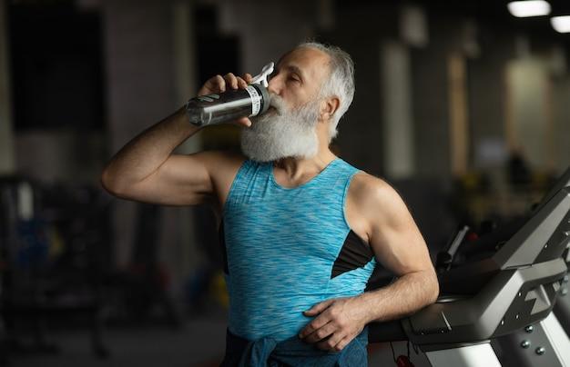 Älterer bärtiger mann in einem fitnessstudio. nach dem training ausruhen