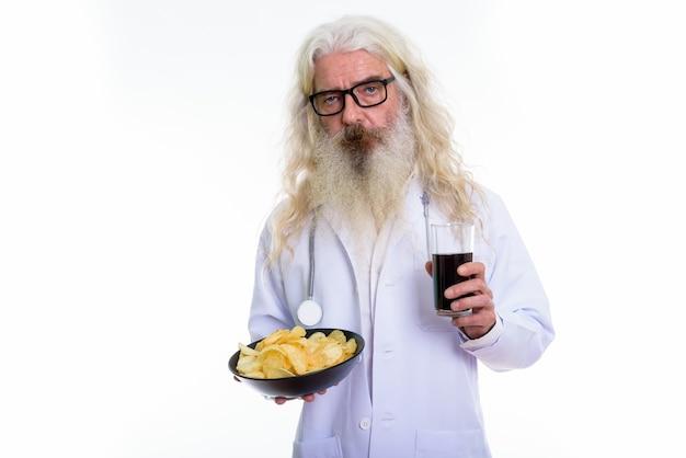 Älterer bärtiger mannarzt, der glas soda hält