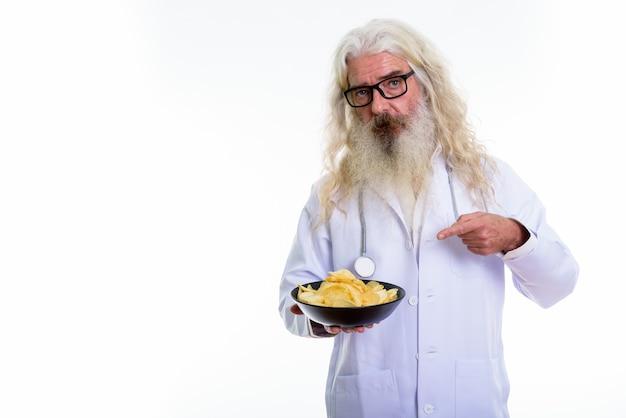 Älterer bärtiger mannarzt, der hält und auf schüssel der kartoffel zeigt