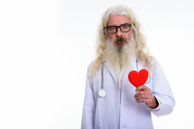 Älterer bärtiger mannarzt, der rotes herz hält