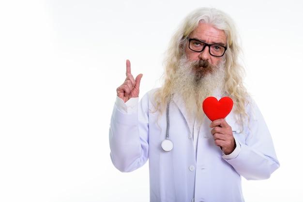 Älterer bärtiger mannarzt, der rotes herz während hält