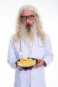 Älterer bärtiger mannarzt, der schüssel kartoffel hält