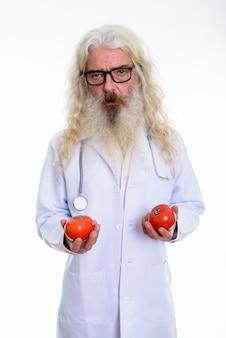Älterer bärtiger mannarzt, der zwei rote tomaten hält