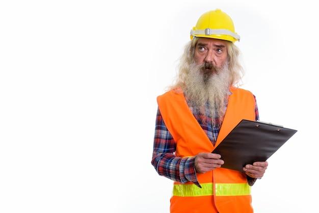 Älterer bärtiger mannbauarbeiter, der klemmbrett hält