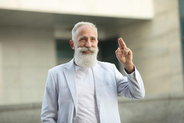 Älterer bartmann, der finger im freien erhebt
