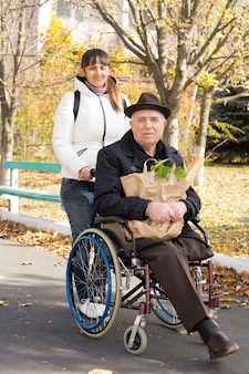Älterer behinderter mann, der einkaufen geht, half durch eine lächelnde attraktive frau