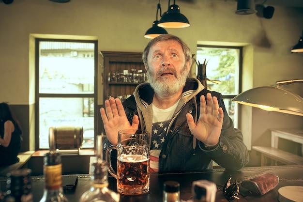 Älterer bettelnder bärtiger mann, der alkohol in der kneipe trinkt und ein sportprogramm im fernsehen sieht. ich genieße meinen lieblingsbrot und mein lieblingsbier. mann mit bierkrug, der am tisch sitzt. fußball- oder sportfan. menschliche gefühle