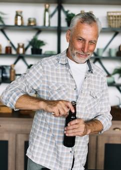 Älterer blinkender mann beim öffnen der kappe der bierflasche
