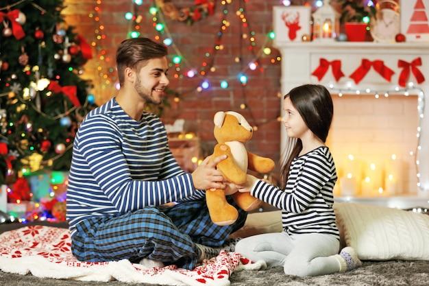 Älterer bruder, der kleiner schwester einen teddybären im weihnachtswohnzimmer gibt