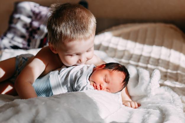 Älterer bruder, der neugeborene kleine schwester küsst