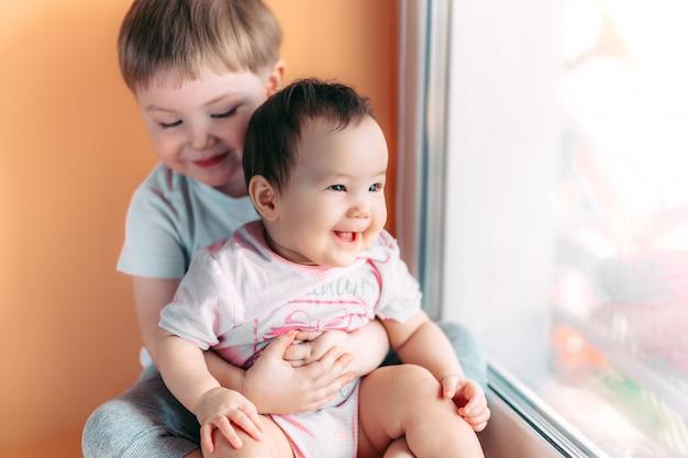 Älterer bruder, der seine kleine schwester umarmt, die zusammen spielt und lächelt.