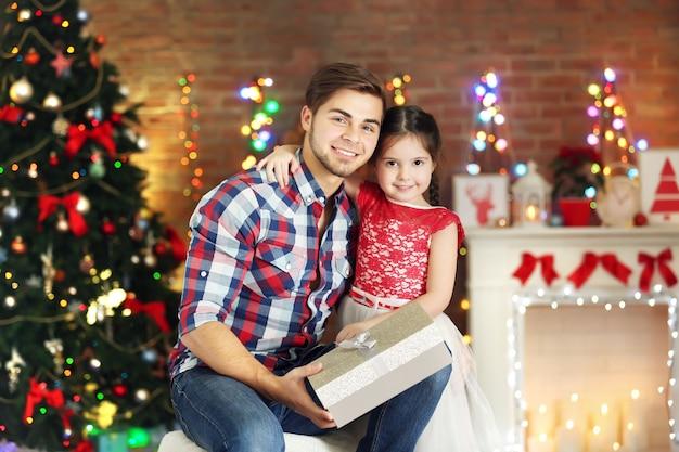 Älterer bruder und kleine schwester sitzen mit geschenk im weihnachtswohnzimmer