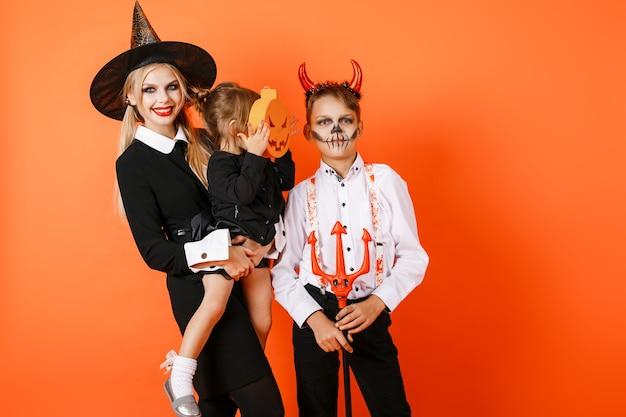 Älterer bruder und schwester, die kleine schwester in den halloween-kostümen halten, die gegen orange wandhintergrund aufwerfen. hochwertiges foto
