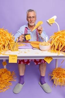 Älterer büroangestellter hat deadline, fühlt stress durch überstunden sitzt am desktop und arbeitet lange im projekt hat eine kaffeepause, umgeben von geschnittenem papier