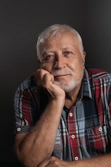Älterer charismatischer mann stützte seinen kopf auf seine hand und lächelte in die kamera, porträt