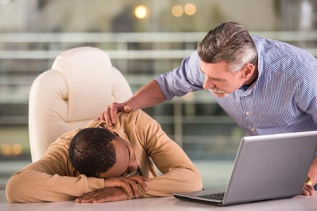 Älterer chef, der schlafende junge afrikanische arbeitskraft im büro aufweckt.