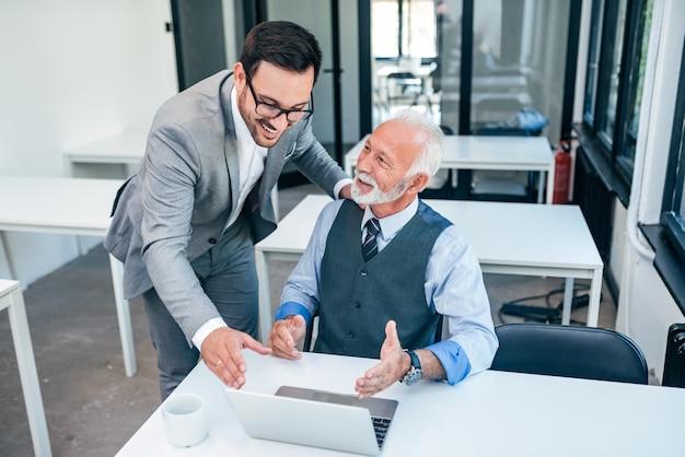 Älterer chef glücklich für gutes on-line-arbeitsergebnis des jungen männlichen geschäftsmannes.