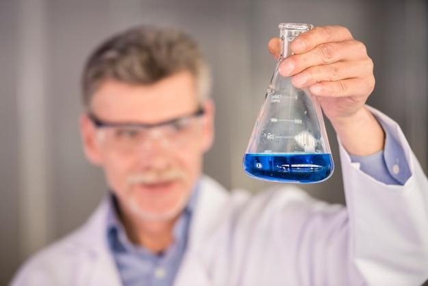 Älterer chemieprofessor, der flasche mit blauer flüssigkeit hält.