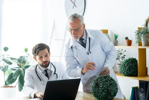 Älterer doktor, der arbeit des kollegen überprüft