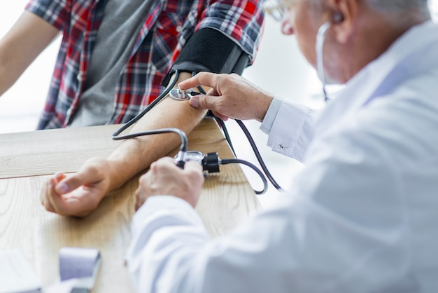 Älterer doktor, der blutdruck misst