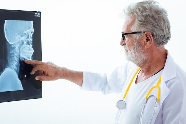 Älterer doktor, der geduldigen kopfkinn- und halsknochenfilmröntgenstrahl schaut