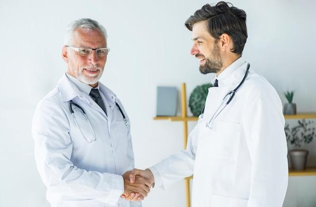 Älterer doktor, der hand des jungen kollegen rüttelt