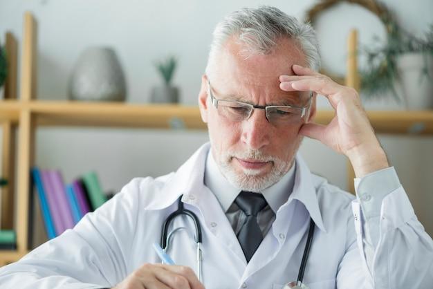 Älterer doktor, der im büro denkt und schreibt