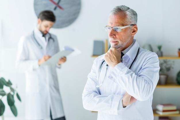 Älterer doktor, der im büro denkt
