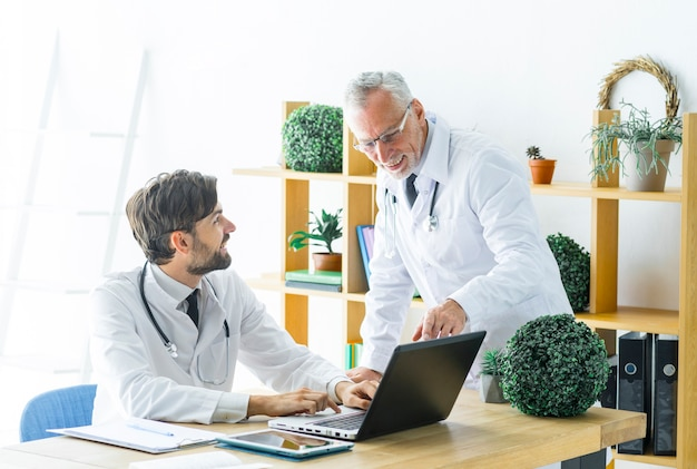 Älterer doktor, der jungem kollegen mit arbeit hilft