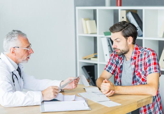 Älterer doktor, der mit patienten im büro spricht