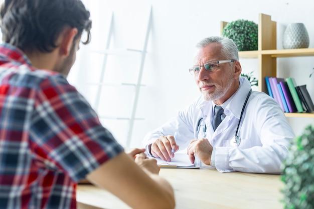 Älterer doktor, der nah auf patienten hört