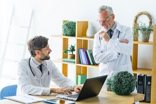 Älterer doktor, der zum jungen kollegen mit laptop lächelt